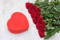 Red box in the heartshaped and roses on a white wooden background.  stock photography