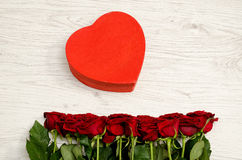 Red box in the heartshaped and roses on a white wooden background, top view.  stock photo