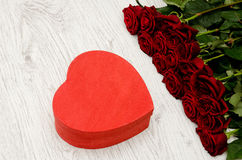 Red box in the heartshaped and roses on a white wooden background, top view.  stock photos