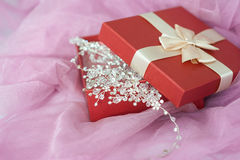 Red box with jewelry on purple veil Royalty Free Stock Images