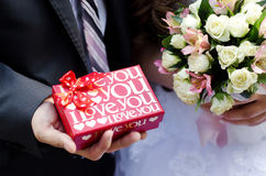 The red box with love in the hands of the groom. The red box with love in the hands of the bride and bouquet in hands of bride closeup Royalty Free Stock Images