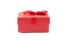 Red box with a ribbon. On a white background Royalty Free Stock Photo