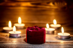 Red box with a ring on the background of burning small candle. Royalty Free Stock Photography