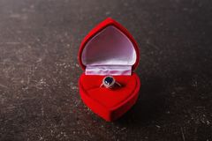 Red box with a silver ring with a black stone Royalty Free Stock Image