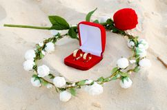 Red box with wedding rings in the center of a wreath of white flowers on the sand and a small rose in the background. Close view Royalty Free Stock Photography