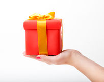 Red box with a yellow ribbon in the hand Stock Image