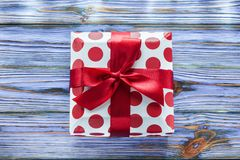 Red boxed gift on vintage wooden board.  stock photo
