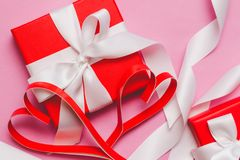 Red boxes with a gift, tied with a white ribbon, and red homemade paper hearts on a pink background. Symbol of Valentine`s Day stock photography
