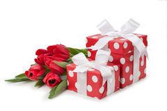 Red boxes with white ribbons and a bouquet of tulips Royalty Free Stock Photography