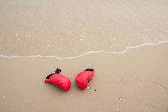 Red boxing glove. On the beach stock photos