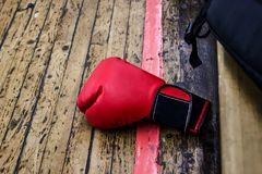 Red boxing glove on the gym floor with wooden covering. Nearby is a black backpack. Sports and training, wrestling and endurance, Stock Photo