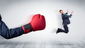 Red boxing glove knocks out little businessman stock photo