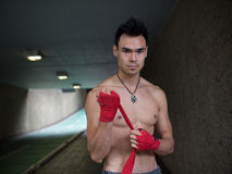 Red Boxing Glove Wraps. A martial arts fighter prepares by wrapping his fist up in boxing glove wraps Stock Photo