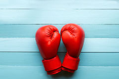 Red boxing gloves. On a blue background stock images