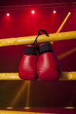Red boxing gloves hangs off the boxing ring Stock Image