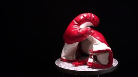 Red boxing gloves rotating on round stool. Red boxing gloves rotation on black background stock video