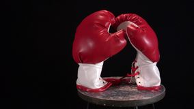 Red boxing gloves rotating on round stool. stock video footage