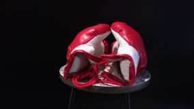 Red boxing gloves rotating on round stool. stock video