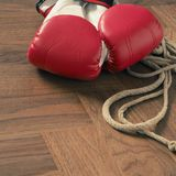 Boxing gloves with skipping rope on wood. Red boxing gloves and skipping rope on a rustic wooden floor in a gym, sports or assertiveness concept stock photography