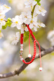 Red bracelet hanging in a blooming branch stock photography