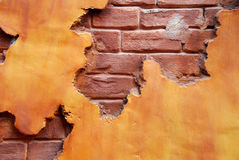 Red Brick. An orange colored stucco wall exposing red brick beneath and makes a great background Royalty Free Stock Image