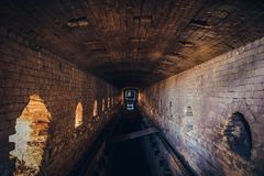 Red brick abandoned underground sewer tunnel with dramatic mysterious atmosphere, inside sewerage. Dark toned royalty free stock photography