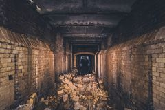 Red brick abandoned underground sewer tunnel with dramatic mysterious atmosphere, inside sewerage. Dark toned Royalty Free Stock Image