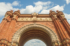 Red brick arch against blue sky on sunny day. View of Arc de Triomf from below against cloudy blue sky on sunny day, Barcelona, Catalonia, Spain Royalty Free Stock Photo