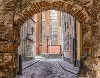 Red brick archway with a cobbled road. royalty free stock photos
