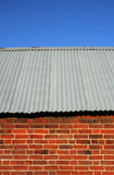 Red brick barn with corrugated iron roof Royalty Free Stock Image