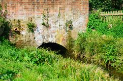 Red brick bridge over small stream. In country Stock Photos