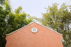 Red brick building in verdant woods on sunny spring day Royalty Free Stock Images