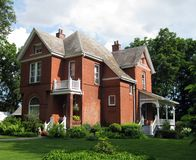 Red-Brick Century Home. A beautiful old red-brick Century home with side porch and second-story balcony, and lush landscaping stock image
