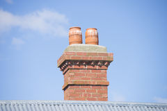 Red brick chimney on roof blue sky copy space Royalty Free Stock Photography