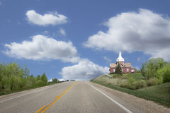 Red brick church sitting on a hill in the distance. Royalty Free Stock Photo