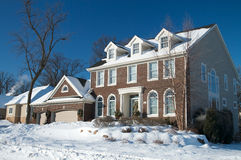 Red Brick Colonial Home in the Winter Snow. A large red brick Colonial home in Winter in Minnesota with a Christmas wreath on the door Royalty Free Stock Photos