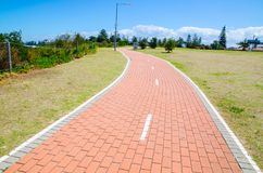 Red brick cycle path and footpath in the park with green field. stock photography