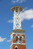 Red brick fire belltower in blue sky Stock Image