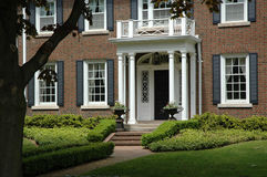 Red Brick House. With black shutters and bright green, manicured lawn / garden with black iron flower urns stock photos