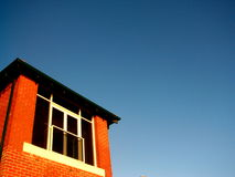 Red brick house and blue sky. Exterior of upper storey of red brick house with blue sky background and copy space royalty free stock photos