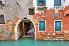 Red brick house on small canal in Venice, Italy. Royalty Free Stock Images