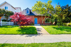 Red brick house with tile roof and maple tree in the front yard. Northwest, USA royalty free stock images