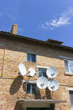 Red brick house wall with satellite dish plate antennas Stock Photography