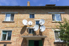 Red brick house wall with satellite dish plate antennas Stock Photos