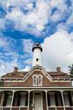 Red Brick House and White Brick Lighthouse Stock Photography