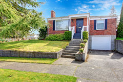 Red brick house with white trim. Brick house with black entrance door, white column porch. VIew of garage and front yard Royalty Free Stock Image
