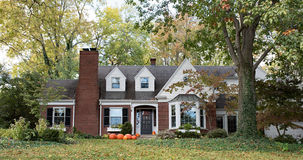 Red Brick House in Wooded Setting with Pumpkins Stock Photo