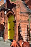 Red brick house with yellow door Royalty Free Stock Photo