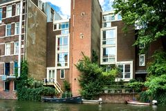 Red brick houses and green vegetation near the canal. Large glass Windows. Many boats on the water near the houses.. Amsterdam. Urban landscape. Summer season stock image