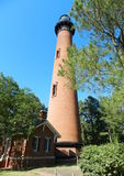 Red brick lighthouse. With red brick house in foreground with trees and bushes Royalty Free Stock Images